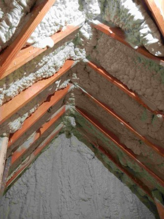 Open cell foam in attic between rafters and covering interior gable.